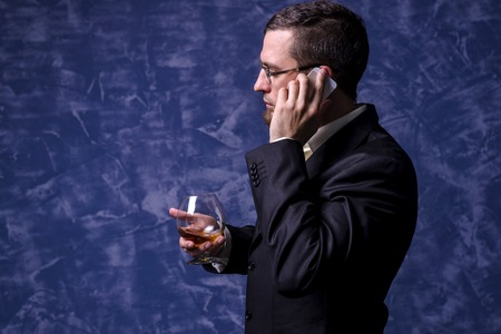 Business man with a glass of brandy and a smartphone. A man in a suit on a blue background. Standard-Bild - 122631943