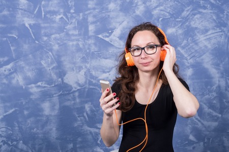 Young woman in glasses listening to music in headphones with the help of a smartphone. Girl in orange headphones with a phone in their hands. Standard-Bild - 122631945