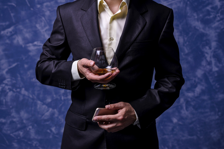 Business man with a glass of brandy and a smartphone. A man in a suit on a blue background.
