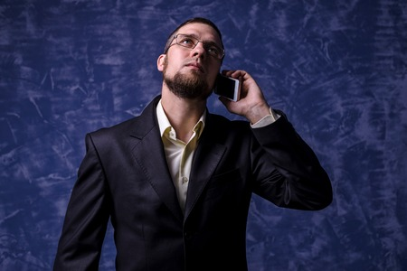 A young man in a suit communicating on a smartphone, blue background. Business man in a suit. Stockfoto