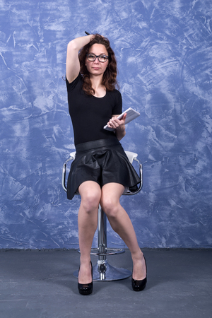 A young woman in black clothes is sitting on a chair on a blue background. Business woman with pen and notepad. Standard-Bild - 122633201