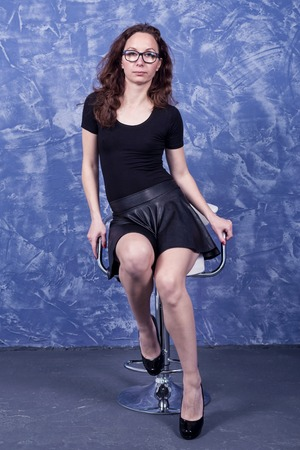 A young woman in a black body and skirt is sitting on a chair. Girl on a gradient blue background.