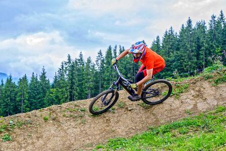 Cyclist riding a mountain bike from a mountain. Man in a bright orange t-shirt making downhill. Extreme sport, MTB. Standard-Bild - 131946190