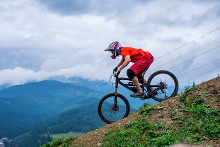 Cyclist riding a mountain bike from a mountain. Man in a bright orange t-shirt making downhill. Extreme sport, MTB.