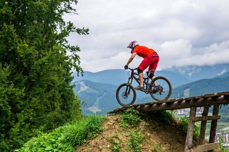 Male cyclist riding a mountain bike in beautiful nature: mountains and blue sky. Downhill, MTB. Extreme sport.