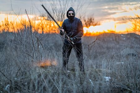 A man in a mask and goggles with a stick in his hands, post-apocalypse. Nuclear war. Zombie.