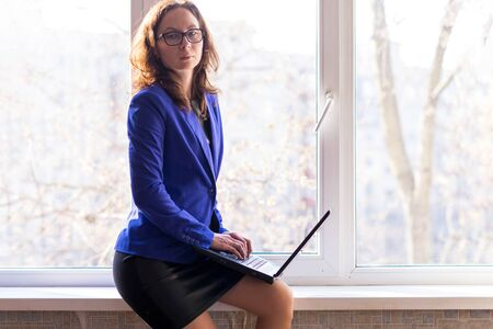 Business woman in glasses working on a laptop while sitting at the window. The concept of remote work. Self isolation. Workaholic.