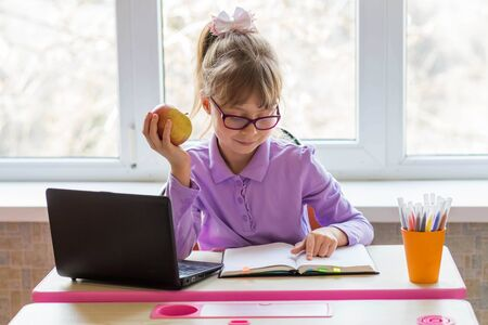 A little schoolgirl sits at a desk and studies on a laptop. The concept of distance learning. Home schooling. Remote learning online.