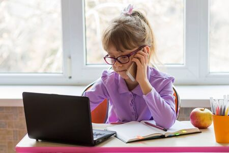First-grader sits at a table talking on the phone and learns remotely on a laptop. The concept of distance learning. Online home schooling during quarantine. Banque d'images
