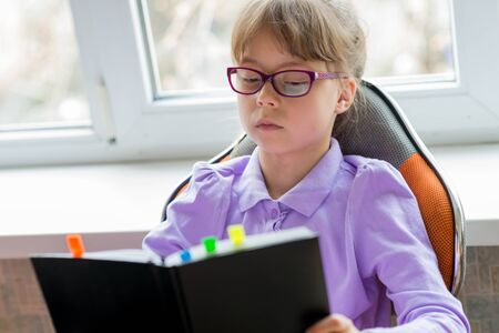 A little schoolgirl in glasses holds a notebook in her hands. Home schooling.