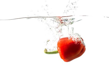 Red pepper with spray of water isolated on a white background. Concept of healthy food, diet. Fresh vegetable.