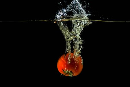 Fresh tomato dropped into water, isolated on dark background. Vegetable.