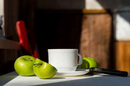 Cup of tea and green apples on a wooden table. Healthy breakfast concept. Still life.