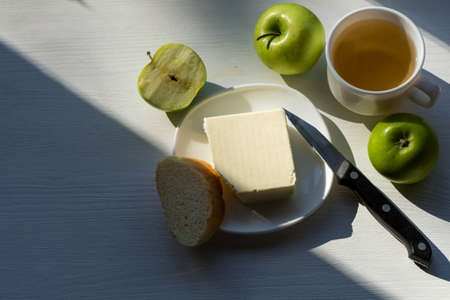 Tasty breakfast: aromatic tea, butter and green apples on a wooden table. Healthy eating concept.