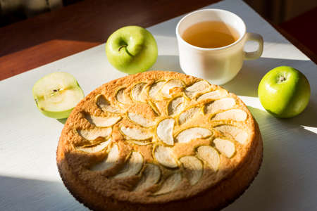 Fragrant apple pie and a cup of tea on a wooden table. Homemade baking.