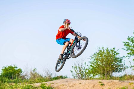 Professional cyclist in a bright T-shirt performs a jump. Extreme sport. Cyclist on a mountain bike.
