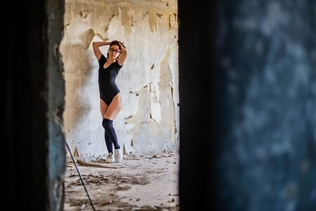 Slender woman in stockings and body. Young woman posing near the wall.