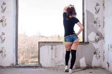 Woman posing in denim short shorts and stockings, rear view. Slender woman. Standard-Bild