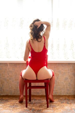 Rear view of a young woman in red stockings and a swimsuit posing on a chair. Slender woman. Standard-Bild