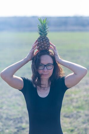 Young woman holds pineapple outdoors. Woman with pineapple. Standard-Bild