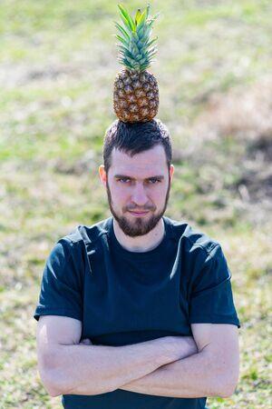 A man holding a pineapple on his head. Ripe pineapple. Standard-Bild