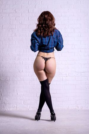 Back view of a young woman in lingerie, stockings and a shirt posing near a wall. Slender woman. Standard-Bild