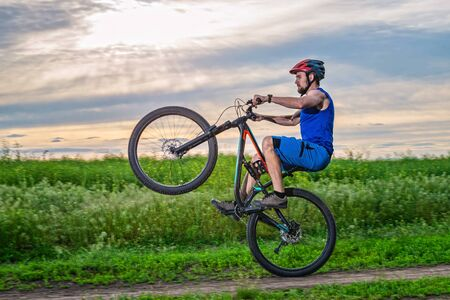 A cyclist in a helmet rides a bicycle on the rear wheel during sunset. Wheelie.