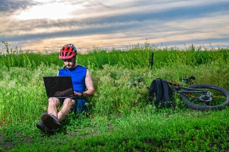 Cyclist working on a laptop while cycling. Remote work outdoors. Active lifestyle, cycling. Workaholic.