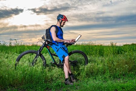 A man working on a laptop on a bike ride. The concept of remote work, freelance. Active lifestyle.