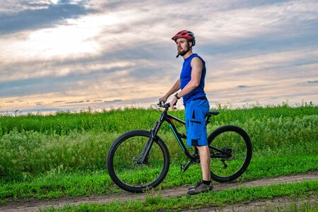 A young man in a helmet with a bicycle standing near the field. Active lifestyle, bike ride.