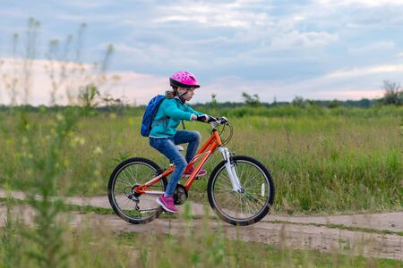 A little girl rides a bicycle on a country road along the meadow. Active lifestyle. Cycling.