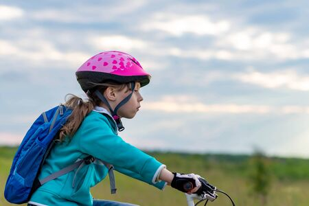 Portrait of a little girl on a bicycle and in a helmet. Active lifestyle. Cycling.