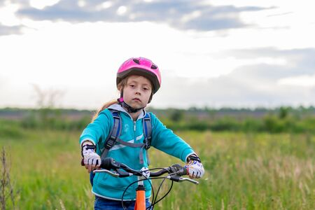 A child in a bicycle helmet stands with a bicycle in the meadow. Active lifestyle. Cycling. Standard-Bild