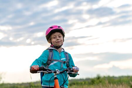 A little girl in a bicycle helmet stands with a bicycle. Active lifestyle. Cycling.