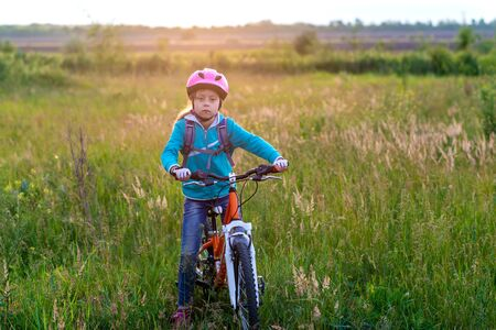 A little girl in a bicycle helmet stands with a bicycle in the meadow. Active lifestyle. Cycling. Standard-Bild