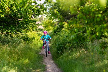 A little girl of about 9 rides a bicycle. Active lifestyle. School summer vacation.