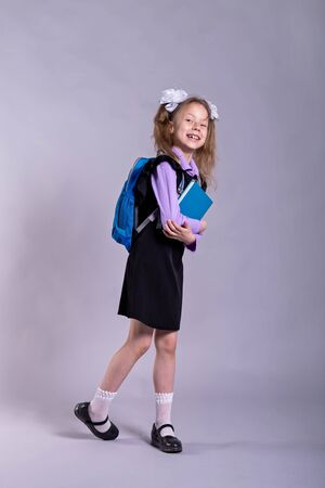 Girl in a school uniform with a book and a backpack on a gray background. Back to school, concept.
