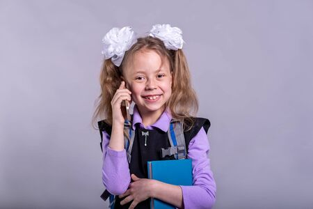 Little girl with bows holding a book and talking on the phone, portrait schoolgirl. Back to school concept.