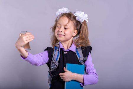 Little girl with bows holding a book and makes selfie phone, portrait schoolgirl. Back to school concept. Standard-Bild