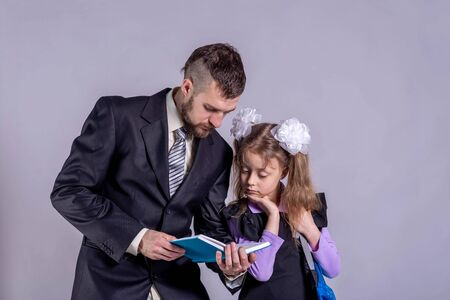 Concept back to school. Dad and daughter are looking at a book on a gray background. Distance learning.