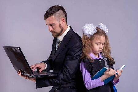Back to school concept. A schoolgirl is holding a book, and dad is a laptop. The concept of distance education.