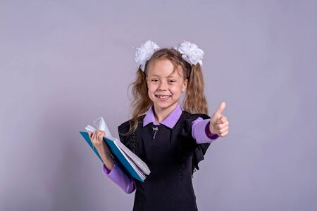 Schoolgirl with ribbons in school uniform holding a book on a gray background, copy space. Back to school concept. Standard-Bild