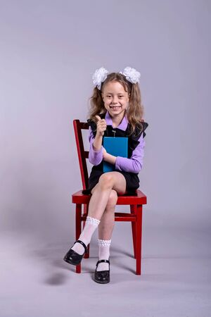 A schoolgirl with bows on her head sits on a chair and holds a book on a gray background. Back to school concept.