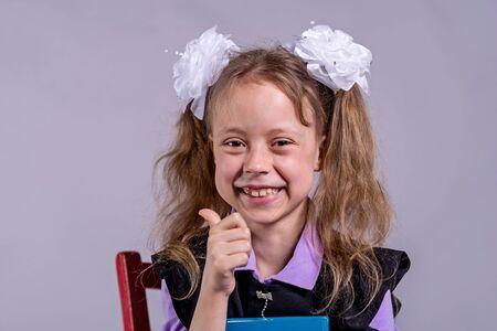 Back to school concept. Little schoolgirl shows ok sign, on a gray background. Standard-Bild