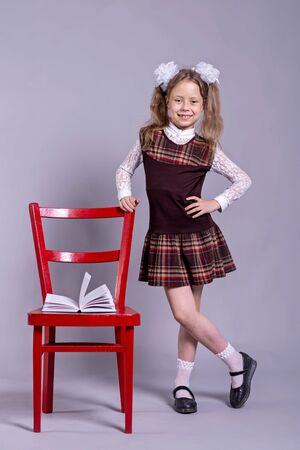 A schoolgirl in a school uniform and bows on her head stands next to a chair on a gray background. Back to school concept. Standard-Bild