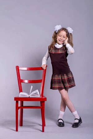 A schoolgirl in a school uniform and bows on her head is standing next to a chair and talking on the phone on a gray background. Back to school concept.