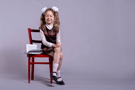 A schoolgirl in a school uniform and bows on her head sits on a chair, on a gray background, copy space. Back to school concept. Standard-Bild