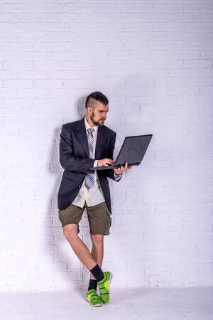 A young man in a suit and shorts works on a laptop while standing near the wall. The concept of remote work. Freelance Standard-Bild