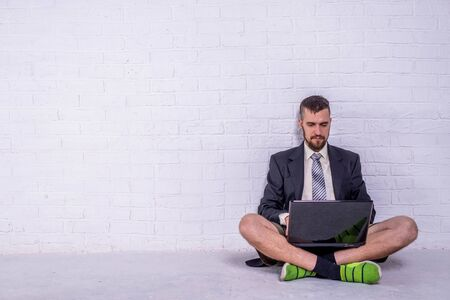 A young man in a suit and shorts works on a laptop while sitting near a wall, copy space. The concept of remote work. Freelance Standard-Bild