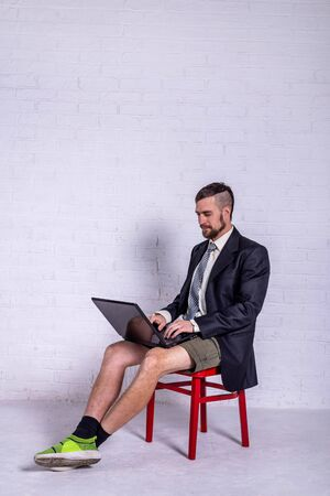 A young man in a suit and shorts works on a laptop while sitting on a chair near the wall. The concept of remote work. Freelance Standard-Bild